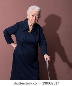Old woman with a cane on brown background