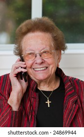 Old woman carries a telephone conversation with mobile phone