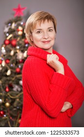 Old woman celebrating New Year, standing near christmas tree at her home. She wears sweater