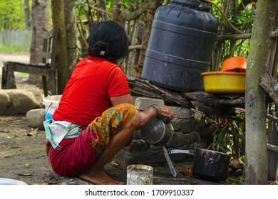 An old woman cleaning dishes from rural Nepal