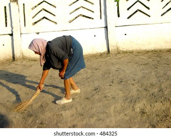 old woman cleaning her yard