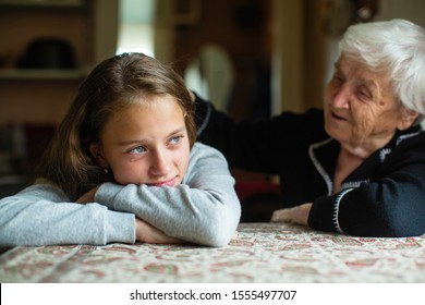 Old woman comforting a crying little girl granddaughter.