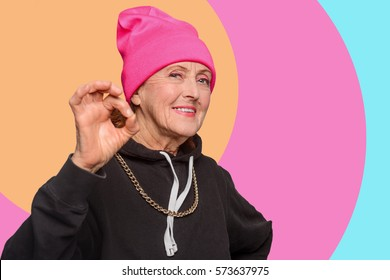 An old woman with a cool ctyle showing a positive gesture. Grandmom says it will be alright. Orange, pink and light blue roundish strips in the background.