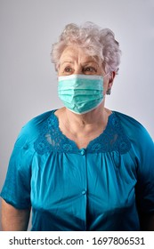 Old woman coronavirus helper. Old lady isolated at home. Home activities. Stay at home. Grandmother sewing face protection masks during quarantine. Old lady wearing protection mask. COVID-19 concept.