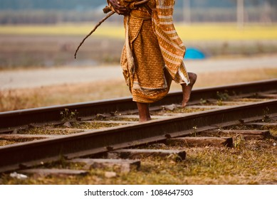 Old woman is crossing a railway tracks isolated unique stock photograph