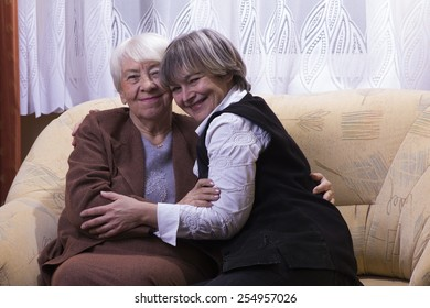 Old woman with daughter hugging