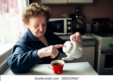 An old woman drinking tea in the kitchen.