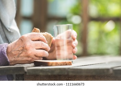 The old woman drinks water and eats bread at an old wooden table in a garden
