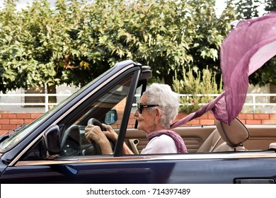 old woman driving a convertible car