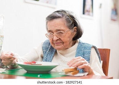 Old woman eating her lunch at home