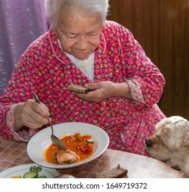 Old woman eating soup at home