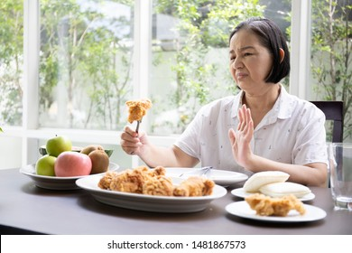Old woman or elder sitting and unhappy eating with junk food or fast food