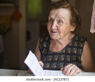 Old woman emotionally talks and reads in a notebook in his house.