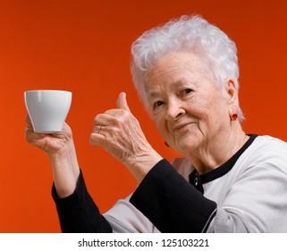Old woman enjoying coffee or tea cup over orange background