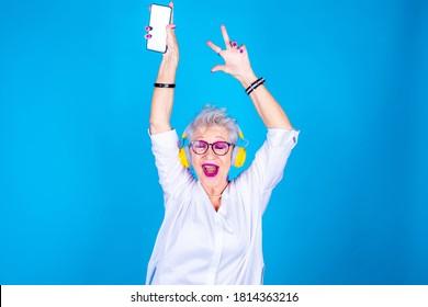 Old woman enthusiastic dancing listening music holding smartphone - Senior grandmoter isolated on blue background enjoying streaming playlist wearing headphones - enjoying, party, celebrating concept