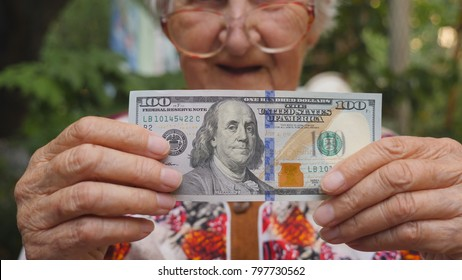 Old woman in eyeglasses showing bill of one hundred dollar into camera and smiling outdoor. Granny holding cash outside. Money concept. Close up Slow motion.
