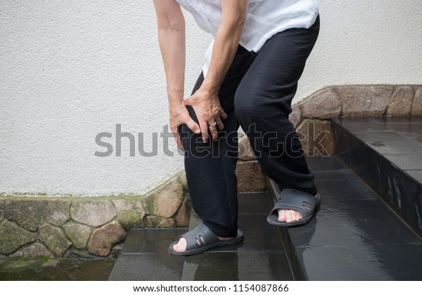 old woman feels pain in knee