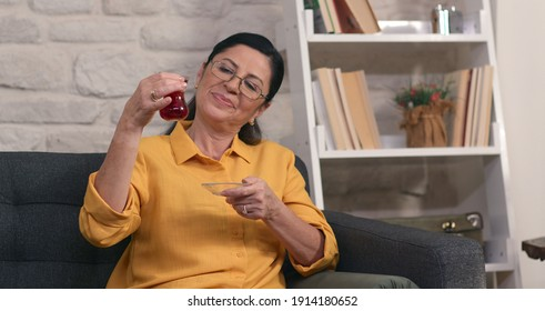 The old woman with glasses is drinking tea at her home. The woman smells the tea in the tea glass in her hand, looks at the color and drinks.