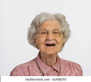 Old woman with glasses and gray hair happy and smiling