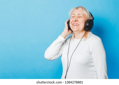 Old woman in glasses and headphones on a blue background. Concept old lady listens to music, audiobooks.