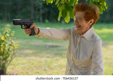 An Old Woman in Glasses Holds a Pistol in the Open Air. Age Eighty Years.