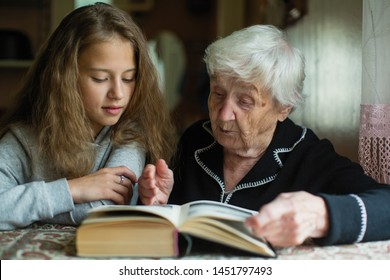 An old woman - a granny with a little girl - granddaughter reading a book.