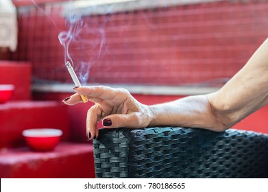 Old woman hand holding cigarette with smoke. Loneliness concept.