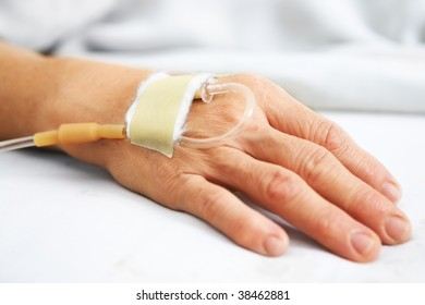 Old woman hand with IV in hospital's bed