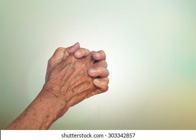 old woman hands praying to god for power on blurred nature background concept.