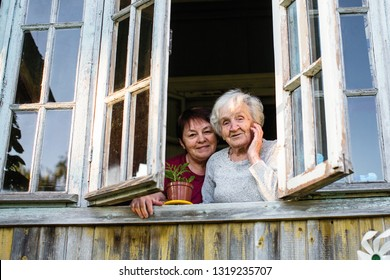 Old woman and her adult daughter from the window of village house.