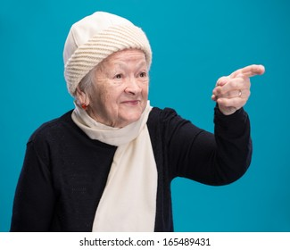 Old woman with her finger pointed aside on blue background