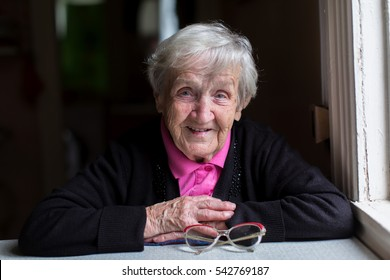 Old woman in her home, looking into the camera.