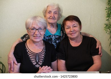 An old woman with her two adult daughter.