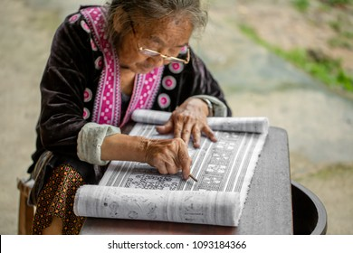 The old woman of Hmong (tribe name) is painting on to the white fabric by the hot wax before being dyed  at Tong Luang village in Chiang Mai , Thailand. This picture is taken on 12 May 2018 at 4 pm.