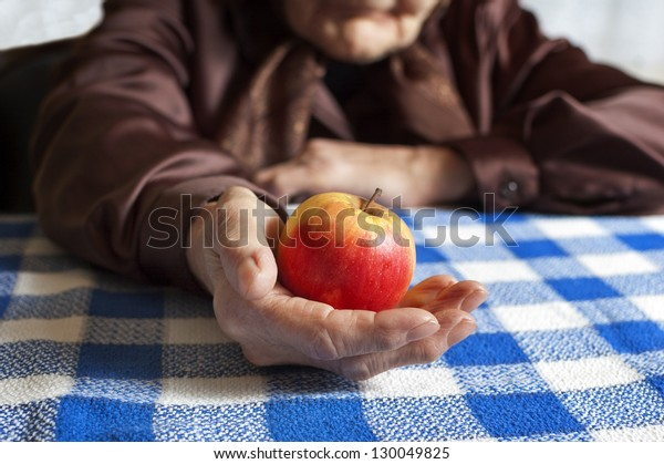 Old woman holding an apple. Selective focus on apple.