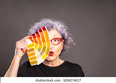 old woman holding a color palette on a gray background