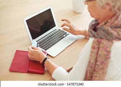 Old woman holding a credit card in front of laptop with blank screen