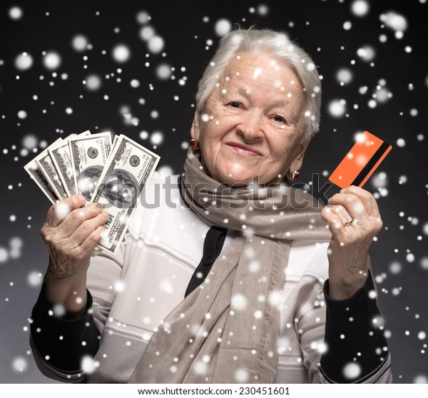 Old woman holding credit card and money. Christmas and holidays concept