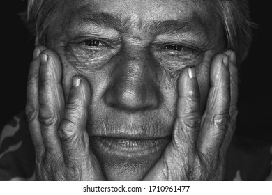 Old woman holding her head in her hands