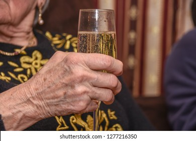 Old woman holds champagne glass in hand