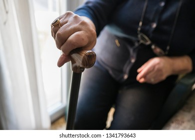 Old woman holds a stick at home