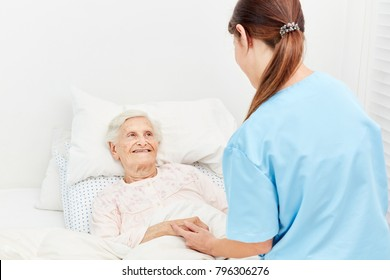 Old woman in hospice or nursing home is being comforted by a nurse