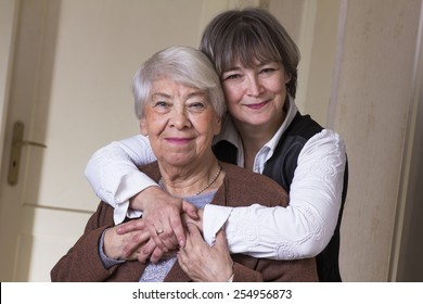 Old woman hugged by daughter.