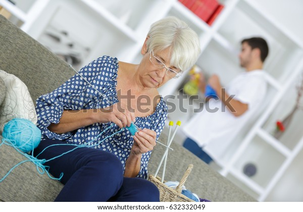 old woman knitting by the window