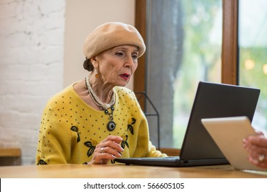 Old woman with laptop. Senior lady indoors. Fix problems with os.