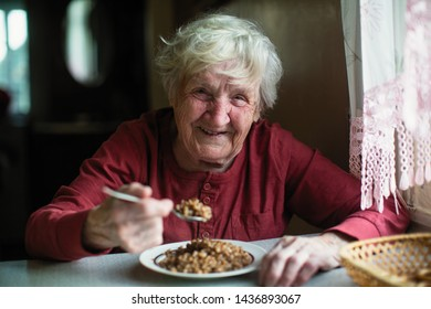 The old woman laughs at dinner at the table in the house.