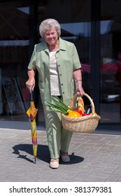 An old woman leaves with her basket a supermarket
