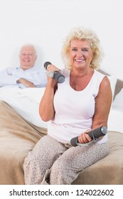 Old woman lifting weights sitting on the bed