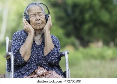 old woman listen on whellchair