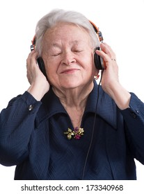 Old woman listening to music in headphones on a white background